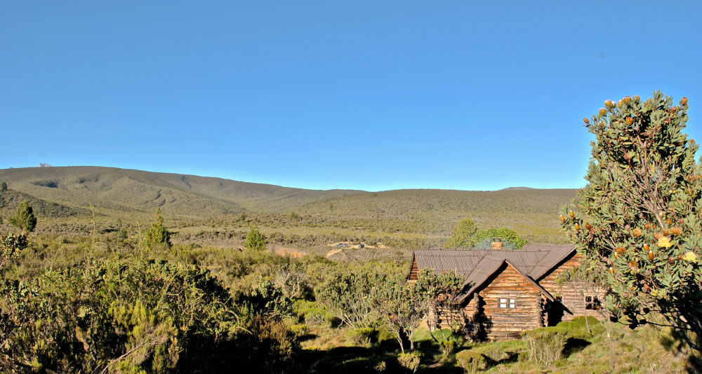 One of the log cabins with Mt. Kenya trying to make an appearance (top left)